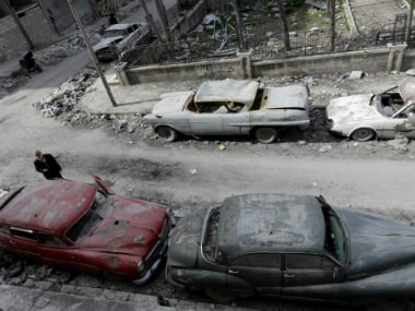 Anis, or Abu Omar, inspecting the cars parked outside his home in Aleppo's formerly rebel-held al-Shaar neighbourhood. News18
