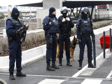 Elite police officers patrol with a police dog at the Orly airport in Paris on Saturday. AP