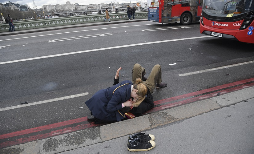 A woman assists an injured person after an incident on Westminster Bridge in London, March 22, 2017. REUTERS/Toby Melville - RTX326E2