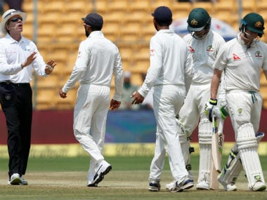 Steve Smith begins to walk off while opposition skipper Virat Kohli has a word with umpire Nigel Llong during the DRS 'brain fade' episode. Reuters