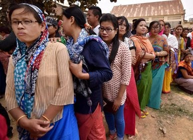 Voters stand in queues at a polling center in Imphal. PTI