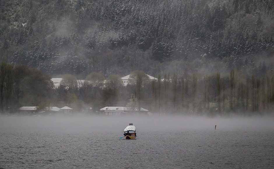 A Kashmiri boatman paddles his shikara amid dense fog on Dal Lake after fresh snowfall in the outskirts of Srinagar, Indian-controlled Kashmir on Thursday. Heavy snowfall and rains have forced authorities in Kashmir to close schools and colleges even as the only all weather road link that connects the Kashmir valley to the rest of India has been cut off. (AP Photo/Dar Yasin)