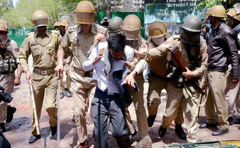 A student being whisked away by police after he was caught from the premises of a college for indulging in stone pelting during protests. Reports said that the students hurled stones, waved Pakistani and Islamic State flags to irk security forces as they were protesting against the Indian force's action against Kashmiri protesters. PTI