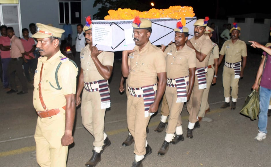 Policemen carry the body of a CRPF personnel at Madurai Airport on Tuesday. PTI