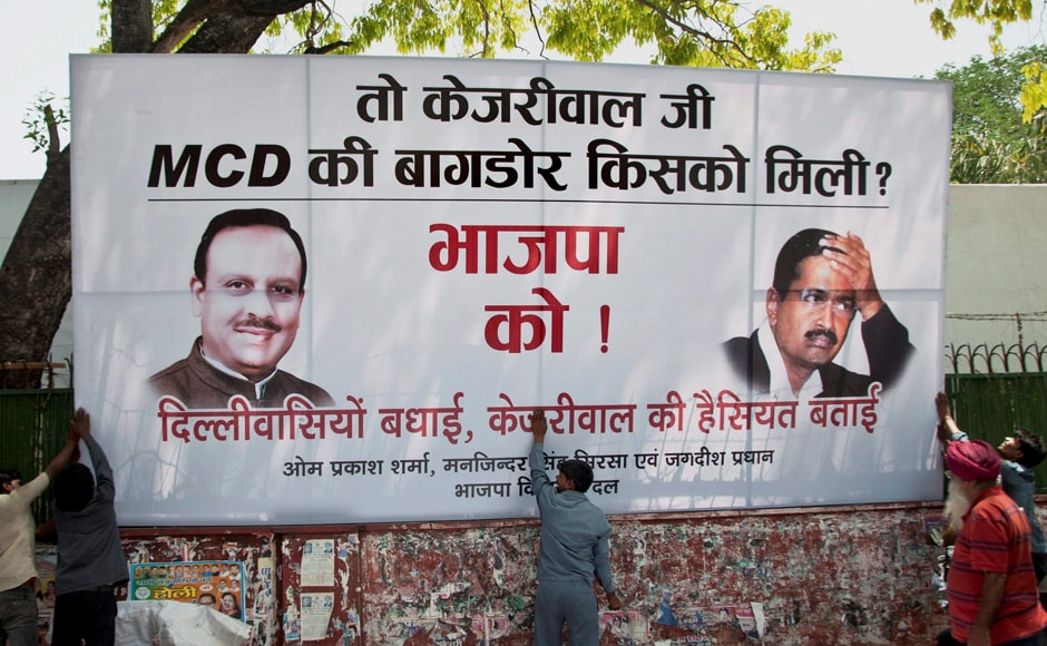 Workers put up a hoarding outside Delhi BJP headquarters in New Delhi on Wednesday. PTI