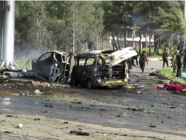 This frame grab from video provided by the Thiqa News Agency, shows rebel gunmen at the site of a blast that damaged several buses and vans at the Rashideen area, a rebel-controlled district outside Aleppo city, Syria, Saturday, April. 15, 2017
