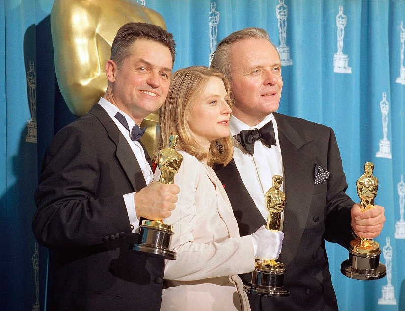 """FILE - In this May 31, 1992 file photo, director Jonathan Demme, left, holds his award for best director, actress Jodie Foster holds her award for best actress, and actor Anthony Hopkins holds his award for best actor for their work on """"Silence of the Lambs,"""" at the Academy Awards in Los Angeles. Demme died, Wednesday, April 26, 2017, from complications from esophageal cancer in New York. He was 73. (AP Photo/Reed Saxon, File)"""