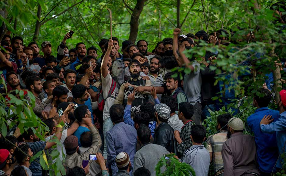 Thousands of mourners defied the security curbs to attend the burial of the rebel commander in his hometown amid anti-India and pro-Independence slogans. In this photo, villagers shout freedom slogans as a rebel, center wearing black, who claimed to have escaped from a gunbattle, speaks as he offers tributes to rebel leader Sabzar Ahmed Bhat who was killed in the gunbattle, in Tral. AP
