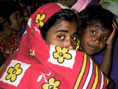 A Bangladeshi woman and her daughter sit in a crowded police van in Howrah. Reuters
