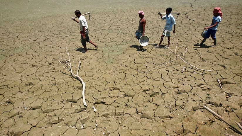 Labourers walk through a parched land of a dried lake on the outskirts of Agartala, capital of India's northeastern state of Tripura April 23, 2013. India may be heading for another bumper grain harvest, if the first forecast for this year's monsoon proves correct, but the rain may be too little - and too late - for southern and western states already parched by the worst drought in four decades. REUTERS/Jayanta Dey (INDIA - Tags: SOCIETY ENVIRONMENT DISASTER) - RTXYXDH