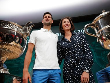 Defending champions Serbia's Novak Djokovic and Spain's Garbine Muguruza pose in front of the cups during the draw of the French Open. AP