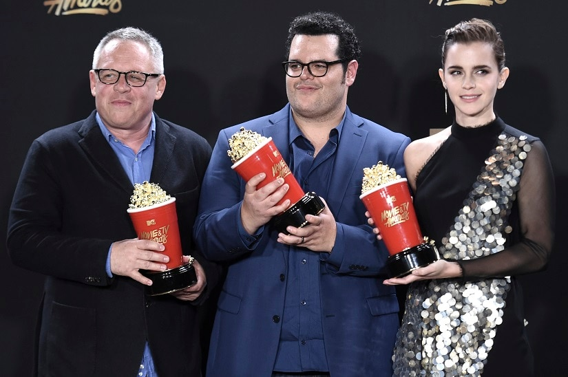 """Bill Condon, from left, Josh Gad and Emma Watson pose with the award for movie of the year for """"Beauty and the Beast"""" in the press room at the MTV Movie and TV Awards at the Shrine Auditorium on Sunday, May 7, 2017, in Los Angeles. (Photo by Richard Shotwell/Invision/AP)"""