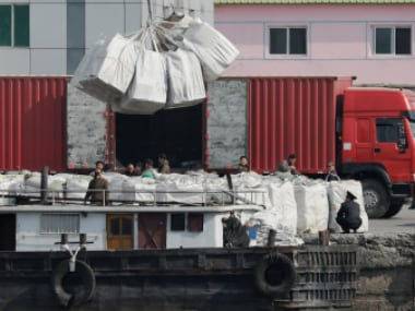 Workers load goods onto a boat on the North Korean side of the Yalu River near Sinuiju, North Korea. Reuters