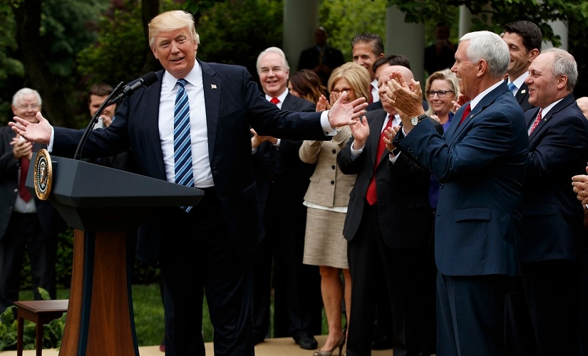 President Donald Trump, accompanied by GOP House members, speaks in the Rose Garden of the White House in Washington on Thursday. AP