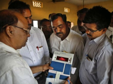 File images of government officials with an EVM. AP