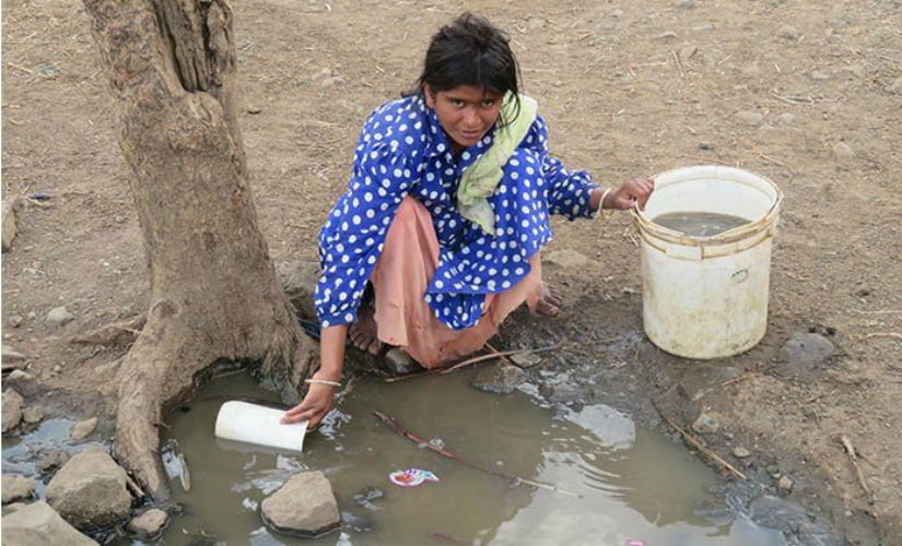 A young woman fills her bucket with dirty water fearing that the handpump might give in anytime. Photo courtesy: Parth MN