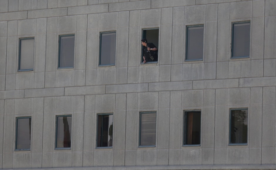 An Iranian policeman looks out of the Parliament building in central Tehran on Wednesday. Tima via Reuters