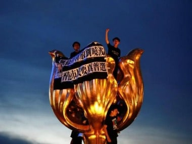 Pro-democracy activists chant slogans on the Golden Bauhinia, a gift from China at the 1997 handover, on Wednesday. Reuters