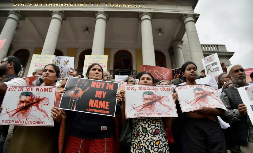"""Citizens hold placards during a silent protest """" Not in My Name """" against the targeted lynching, in Bengaluru. PTI"""