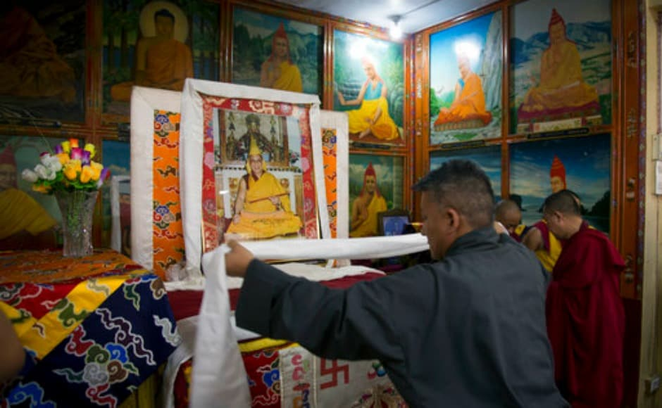 An exile Tibetan government official offers a ceremonial scarf 'khatag' in front of a portrait of the Dalai Lama to mark the Tibetan leader's 82nd birthday in Dharamsala. AP
