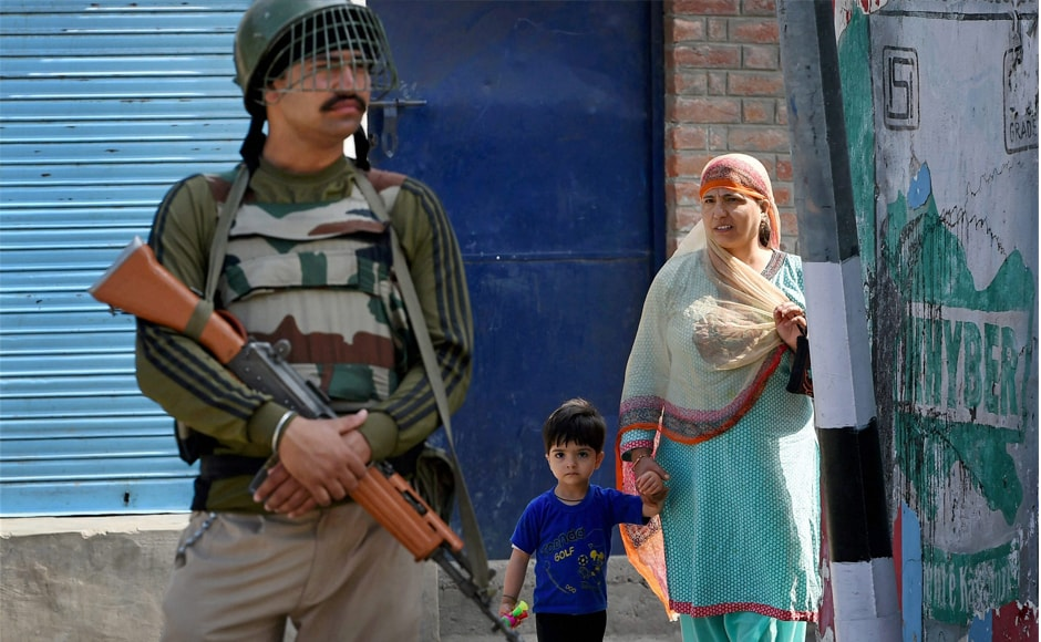 A woman and her son look on as a security guard stands at a road during curfew. Shops and business establishments remained closed and traffic was off the roads at Banihal and Bhaderwah in Ramban and Doda districts following a shutdown call that was given by a religious organisation. PTI