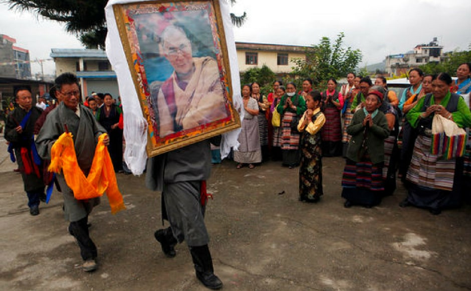 A Tibetan man carries a portrait of the Dalai Lama as members of the community gather to celebrate his 82nd birthday at a Tibetan camp in Lalitpur, Nepal. AP