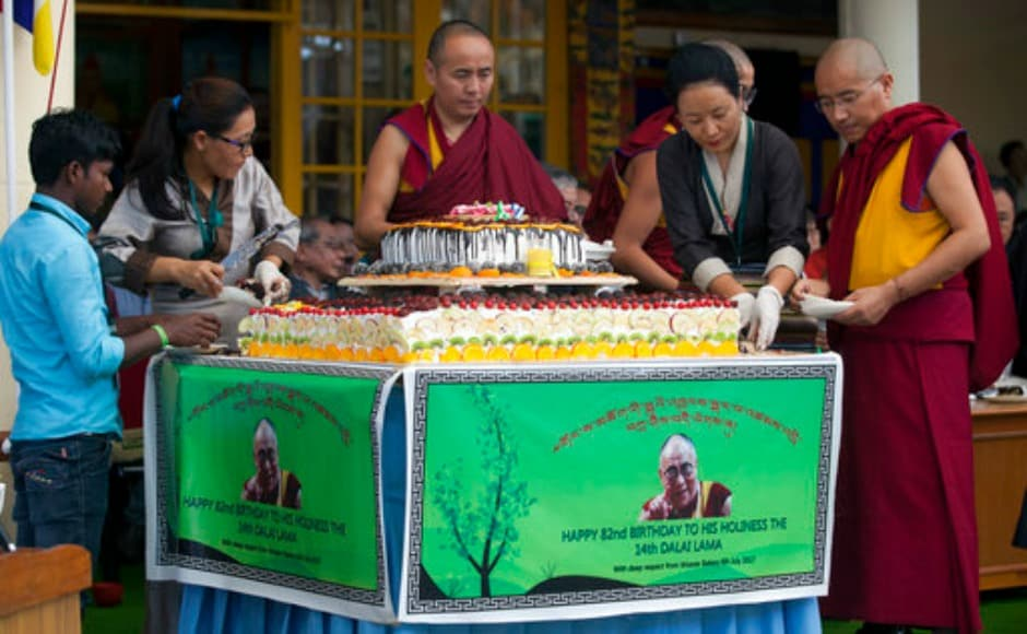 Exile Tibetan volunteers cut a large cake to be distributed among the crowd as they mark the 82nd birthday of the Dalai Lama in Dharamsala on Thursday. AP