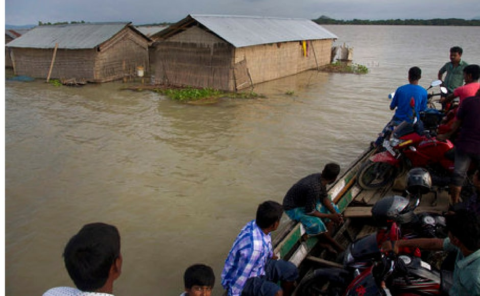Daily commuters wade through flood waters in Assam. Over 3.5 lakh people have been affected in 13 districts of the state. Reuters