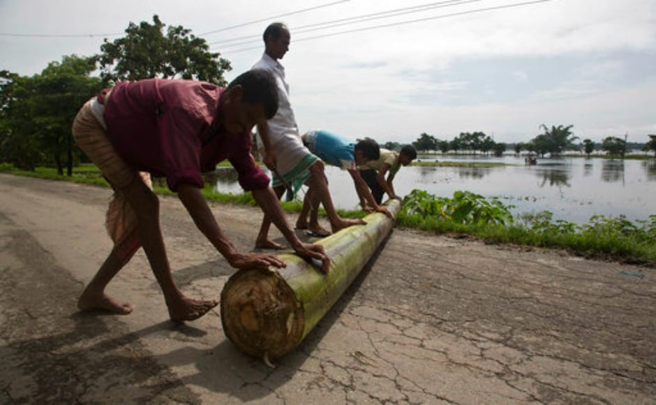 Villagers push the trunk of a banana plant as they prepare to make a banana raft to cross flood waters in Mayong village, east of Guwahati in Assam. AP