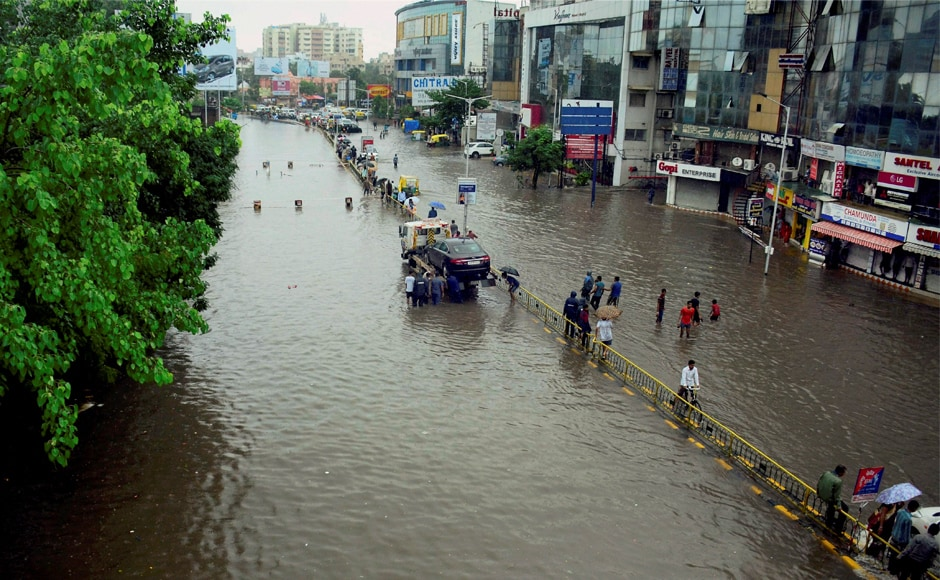 People make their way through a flooded street following heavy downpour in Ahmedabad. Officials said the number of people who lost their lives in Gujarat in the deluge stood at 123. PTI