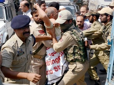 Security personnel detain traders during a protest against the implementation of Goods and Services Tax (GST) during Special Session of Legislative Assembly, in Srinagar on Tuesday. PTI