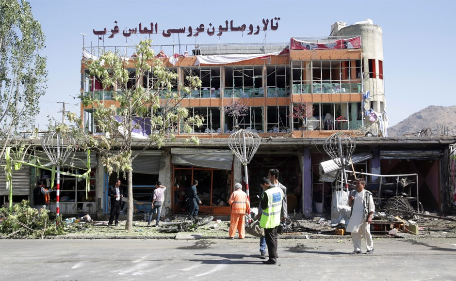Municipality workers clean up in front of a wedding hall at the site of the attack in Kabul. The Taliban claimed responsibility for the blast, which came just before 7 am. The group rarely claims attacks with high civilian casualties but does frequently target government employees. AP