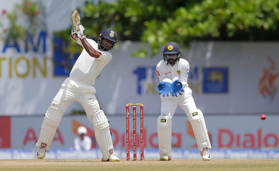 India's Abhinav Mukund plays a shot as Sri Lanka's Niroshan Dickwella watches during the third day's play of the first test cricket match between India and Sri Lanka in Galle, Sri Lanka, Friday, July 28, 2017. (AP Photo/Eranga Jayawardena)