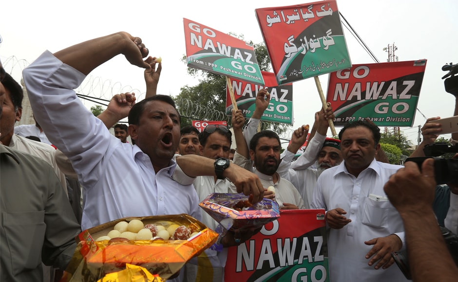 Supporters of opposition parties share sweets to celebrate the Nawaz Sharif's dismissal in Peshawar, Pakistan. Opposition party members began chanting 'Go, Nawaz, Go' after the Supreme Court verdict was announced. AP
