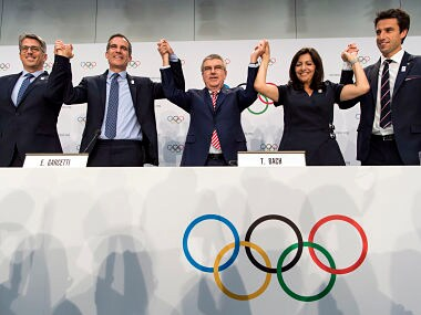 From left, Casey Wasserman, Chairman of Los Angeles 2024, Eric Garcetti, Mayor of Los Angeles, International Olympic Committee, IOC, President Thomas Bach, Anne Hidalgo, Mayor of Paris, Tony Estanguet, Co-president of Paris 2024, gesture, during a press conference after the International Olympic Committee (IOC) Extraordinary Session, at the SwissTech Convention Centre, in Lausanne, Switzerland, Tuesday, July 11, 2017. If they can agree who goes first, Paris and Los Angeles will be awarded the 2024 and 2028 Olympics. International Olympic Committee members voted unanimously to seek a consensus three-way deal between the two bid cities and the IOC executive board. Talks will open with Paris widely seen as the favorite for 2024. (Jean-Christophe Bott,Keystone via AP)