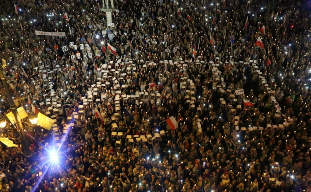 Crowds of thousands gathered in Warsaw, Krakow and other Polish cities chanted 'free courts' and waved placards protesting against the draft bill. AP