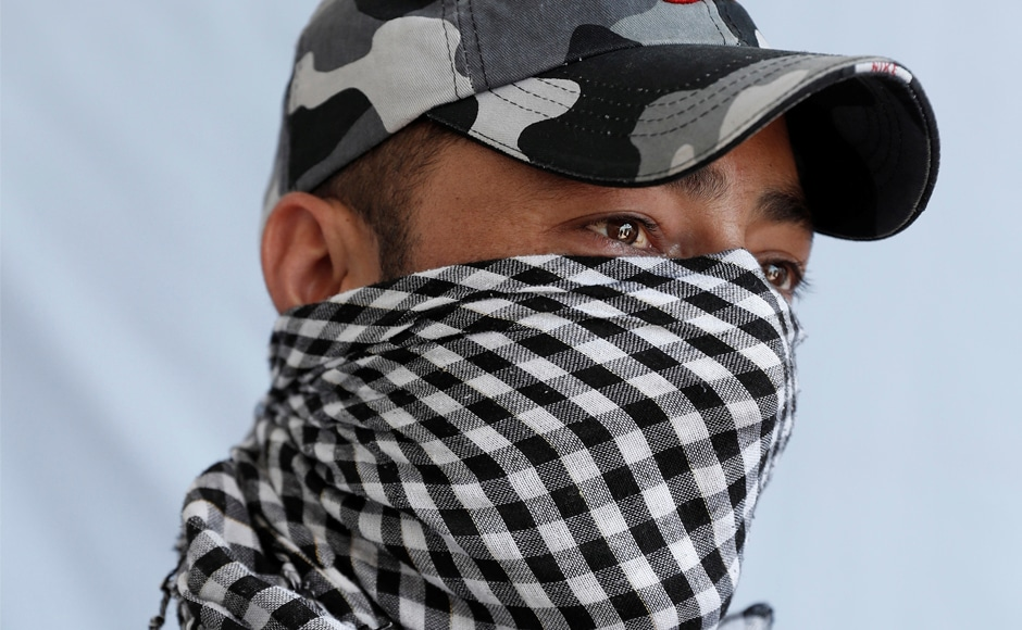 A 24-year-old police officer, who asked to remain anonymous, poses for a portrait in Kashmir.