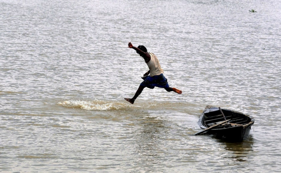 A boy jumps from his boat into the flood waters in Morigaon of Assam. PTI