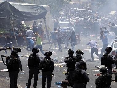 Palestinians running away from tear gas in Jerusalem. AP