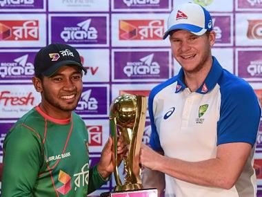Australian cricket captain Steven Smith (R) and Bangladesh captain Mushfiqur Rahim (L)hold the tournament trophy at the Sher-e-Bangla National Cricket Stadium in Dhaka on August 26, 2017. / AFP PHOTO / Munir UZ ZAMAN