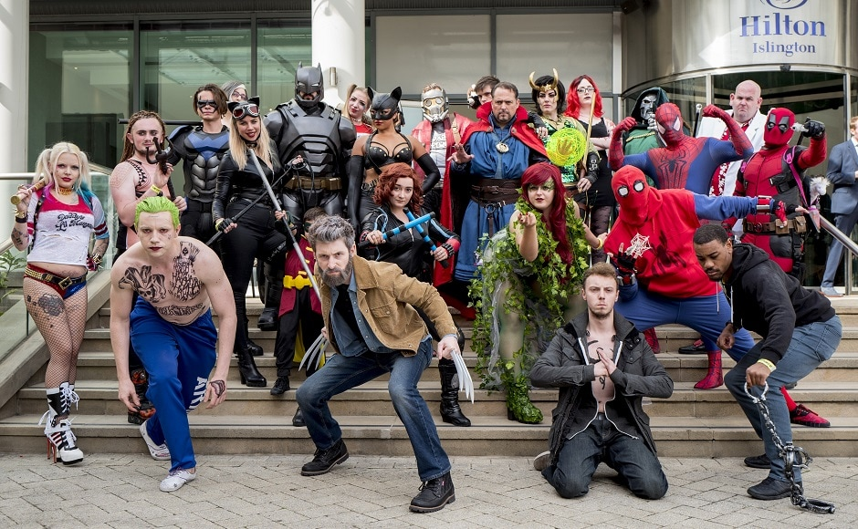 Cosplayers dressed as DC Universe characters pose for photographers as they attend London Super Comic Convention. AFP PHOTO
