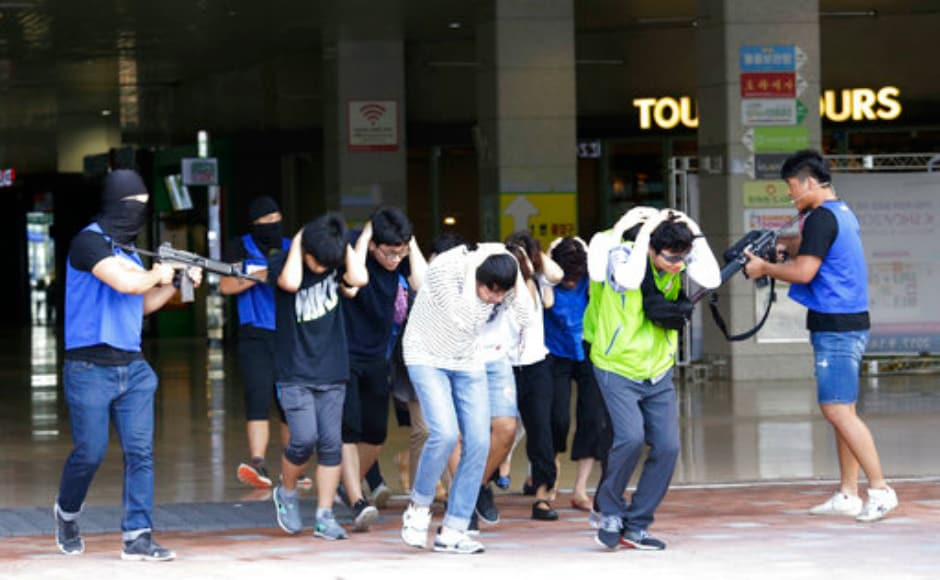 As part of the exercise, mock terrorists threaten supposed hostages at a shopping centre in Goyang, South Korea. AP