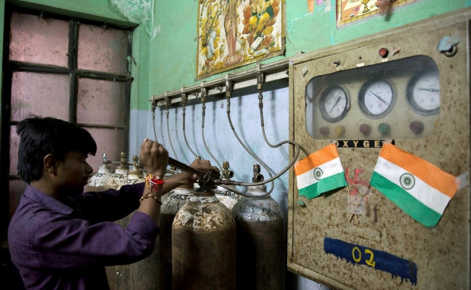 A hospital staff member checks newly arrived oxygen cylinders at Baba Raghav Das Medical College Hospital in Gorakhpur. District magistrate Rajiv Rautela said on Saturday that the deaths of the children being treated for different ailments were due to natural causes. He denied that an insufficient oxygen supply led to their deaths. AP