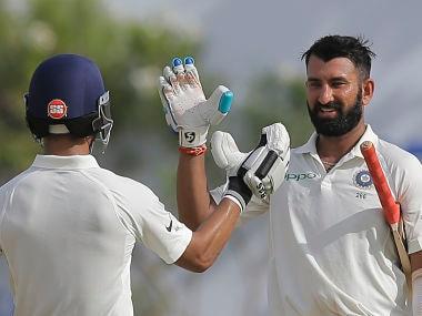 India's Cheteshwar Pujara celebrates with with Ajinkya Rahane after scoring his 13th Test century. AP