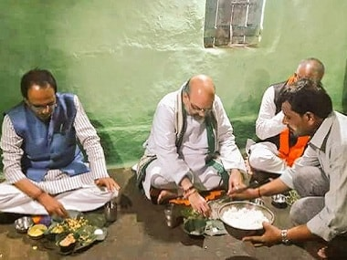 Amit Shah and Shivraj Singh Chouhan having lunch with a family in Bhopal. Image courtesy: Twitter/@AmitShah