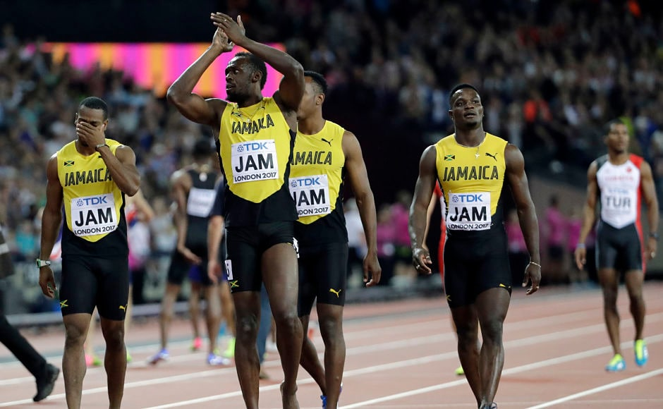 Jamaica's Usain Bolt, second left, walks with his teammates acknowledging the crowd that rallied behind him despite his having to pull out of the race with just 50 metres to spare in the last lap due to a hamstring injury. AP