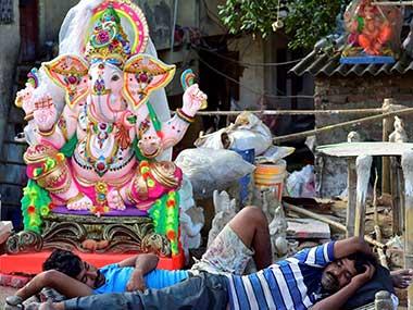 Artists sleep near idols of Ganpati prepared for Ganesh festival in New Delhi on Sunday. PTI