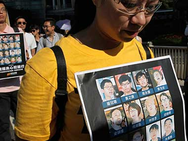 Protesters carry images of activists who were put in jail during a rally to support young activists Joshua Wong, Nathan Law and Alex Chow in downtown Hong Kong on Sunday. AP
