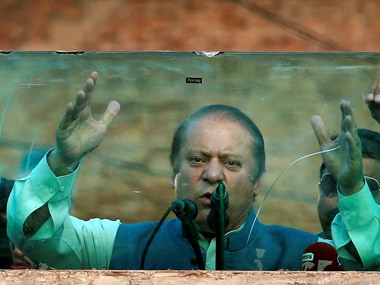 Deposed Pakistani Prime Minister Nawaz Sharif addresses his supporters behind glass during a rally in Jhelum, Pakistan on Thursday. AP