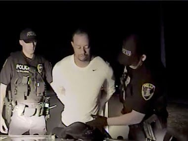 Tiger Woods is seen handcuffed and searched by police officers in this still image from police dashcam video in Jupiter, Florida, U.S. on May 29, 2017. Video released on May 31, 2017. Courtesy Jupiter Police Department/Handout via REUTERS ATTENTION EDITORS - THIS IMAGE WAS PROVIDED BY A THIRD PARTY. EDITORIAL USE ONLY. - RTX38GP9